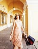 Jeune jolie femme de sourire dans le chapeau avec des sacs sur des achats au magasin Images stock