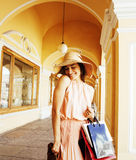 Jeune jolie femme de sourire dans le chapeau avec des sacs sur des achats au magasin Photos libres de droits