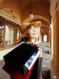 Jeune jolie femme de sourire dans le chapeau avec des sacs sur des achats au magasin Image stock