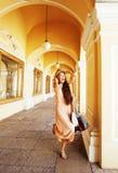 Jeune jolie femme de sourire dans le chapeau avec des sacs sur des achats au magasin Photographie stock libre de droits