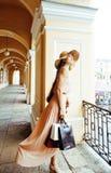 Jeune jolie femme de sourire dans le chapeau avec des sacs sur des achats au magasin Photo stock