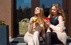 Jeune jolie femme deux riant dehors et café potable Li Image libre de droits