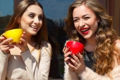 Jeune jolie femme deux riant dehors et café potable Li Images libres de droits