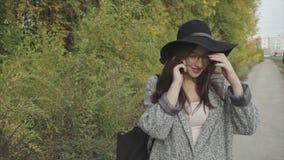 Jeune jolie femme en chapeau noir et verres appelant à son ami extérieur clips vidéos