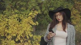 Jeune jolie femme en chapeau noir et verres dactylographiant des sms à son ami extérieur banque de vidéos