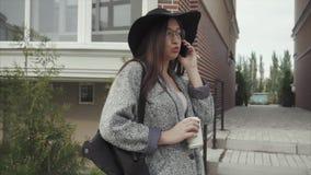 Jeune jolie femme en chapeau noir et verres parlant au téléphone extérieur banque de vidéos