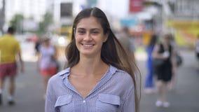 Jeune jolie femme heureuse avec de longs cheveux souriant à l'appareil-photo et à la position sur la rue urbaine banque de vidéos