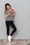 Jeune jolie femme heureuse causant par le téléphone et le café potable Photo stock