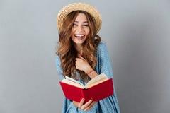 Jeune jolie femme heureuse lisant un livre regard de l'appareil-photo Photos libres de droits