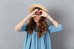 Jeune jolie femme heureuse montrant le geste de coeur regard de l'appareil-photo Images stock