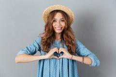 Jeune jolie femme heureuse montrant le geste de coeur regard de l'appareil-photo Images libres de droits