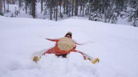 Jeune jolie femme heureuse portant le costume drôle de tigre se situant en congère dans la forêt d'hiver Photo stock
