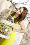 Jeune jolie femme intelligente posant avec une cage Image stock