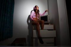 Jeune jolie femme latine s'asseyant dans une chambre d'hôtel Photo libre de droits
