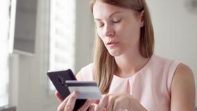 Jeune jolie femme s'asseyant à la maison Achat en ligne avec la carte de crédit sur le mobile Consommationisme en ligne banque de vidéos