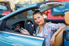 Jeune jolie femme s'asseyant dans une voiture convertible avec les clés dedans Photo stock