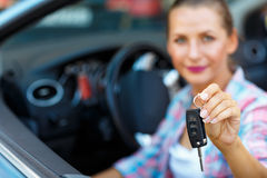 Jeune jolie femme s'asseyant dans une voiture convertible avec les clés dedans Photographie stock libre de droits