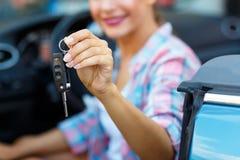 Jeune jolie femme s'asseyant dans une voiture convertible avec les clés dedans Images libres de droits