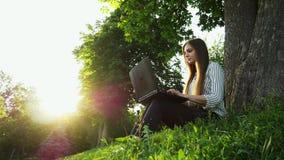 Jeune jolie femme s'asseyant sur l'herbe près de l'arbre et du carnet d'utilisation, ordinateur portable ouvert de fille banque de vidéos