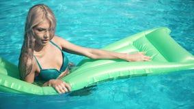 Jeune jolie femme se trouvant sur le matelas d'air dans la piscine Photo stock