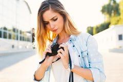 Jeune jolie femme semblant inquiétée à sa caméra de cru tandis qu'u photographie stock libre de droits