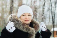 Jeune jolie femme sur l'oscillation en parc d'hiver Photographie stock libre de droits
