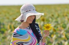 Jeune jolie femme sur le gisement de floraison de tournesol en été images libres de droits