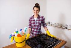 Jeune jolie femme tenant des outils et des produits de nettoyage dans le seau photographie stock