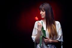 Jeune jolie femme tenant la tulipe rouge Photo stock