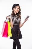 Jeune jolie femme tenant un téléphone portable pour faire des emplettes en ligne au-dessus du fond blanc images libres de droits