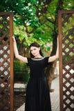 Jeune jolie fille élégante sexy dans l'extérieur noir de robe un jour ensoleillé photo stock
