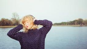 Jeune jolie fille ayant l'amusement écoutant la musique Image stock