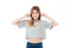 Jeune jolie fille bloquant ses oreilles avec l'irritation Image libre de droits