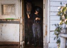 Jeune jolie fille - cheval prepring pour la monte Photographie stock libre de droits