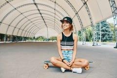 Jeune jolie fille de sourire avec un longboard photographie stock