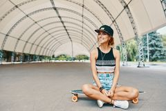 Jeune jolie fille de sourire avec un longboard photo stock