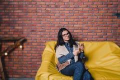 jeune jolie fille en verres avec un téléphone sur un sofa contre photographie stock
