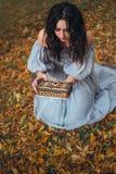 Jeune jolie fille incertaine avec des défis de cheveux noirs pour ouvrir un cercueil, ne sachant pas la punition terrible des die photo libre de droits
