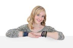 Jeune jolie fille jugeant une plaquette blanc d'isolement sur le blanc Photographie stock