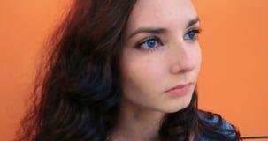 Jeune jolie fille réfléchie avec de longs cheveux bruns au-dessus de fond orange de mur banque de vidéos