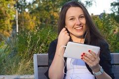 Jeune jolie fille s'asseyant sur le banc en parc et écoute Images stock
