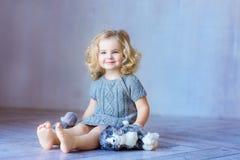 Jeune jolie fille s'asseyant sur un plancher Sourire d'intérieur Fille d'enfant en bas âge images stock