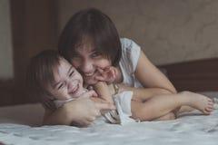 Jeune jouer d'une chevelure foncé d'enfant en bas âge de mère et de fille, caressant Image libre de droits