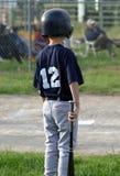 Jeune joueur attendant à 'bat' Image stock
