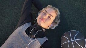 Jeune joueur de basket féminin rêveur se trouvant sur la cour et la musique de écoute par des écouteurs, boule plaçant près de el banque de vidéos