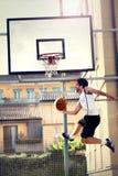 Jeune joueur de basket jouant avec de l'énergie Photographie stock libre de droits