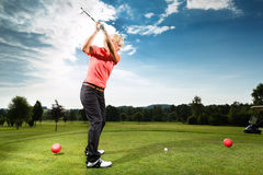 Jeune joueur de golf sur le cours faisant l'oscillation de golf Photo stock