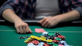 Jeune joueur de poker pariant toutes les puces espérant gagner, casino risqué jouant images stock