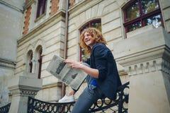 Jeune journal rougeâtre de lecture d'homme près du bâtiment de style ancien photographie stock