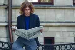 Jeune journal rougeâtre de lecture d'homme près du bâtiment de style ancien photographie stock libre de droits